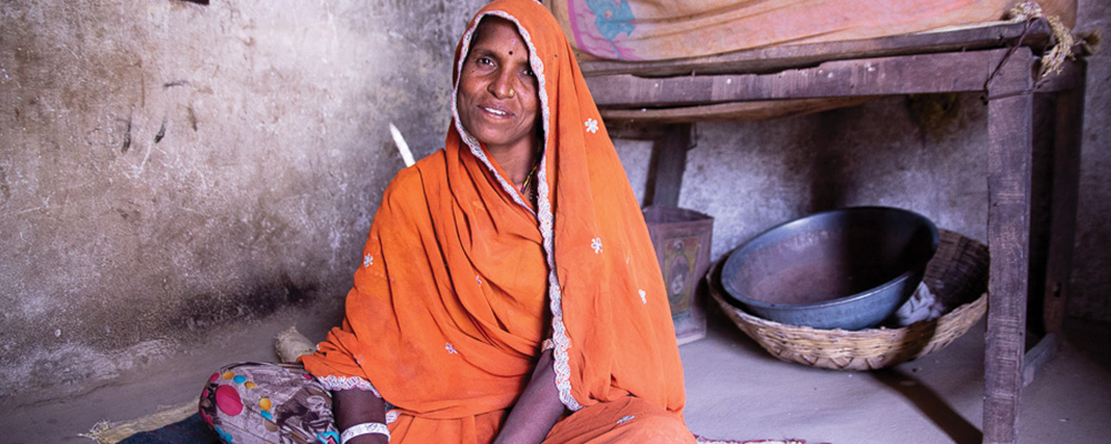 A mother sits in her home in Kalinjar.