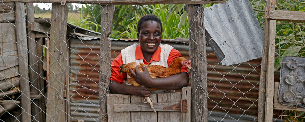 A woman smiles and holds a chicken.