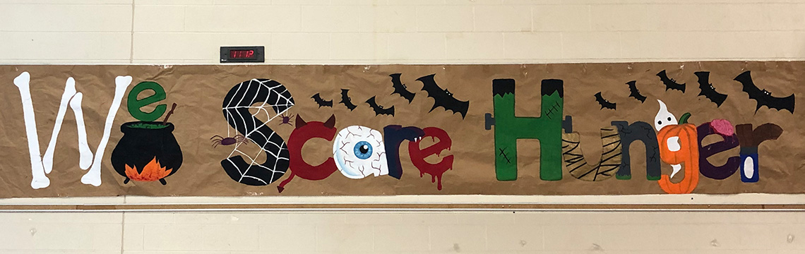 A WE Scare Hunger banner hangs in the cafeteria.