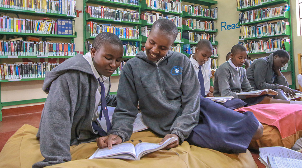 Local students reading in a library in a WE Villages partner community