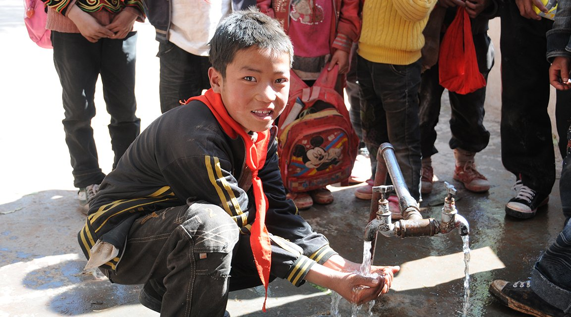 A boy using a newly built water filter