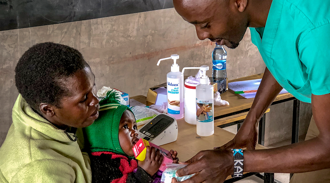 A doctor attends to a mother's infant
