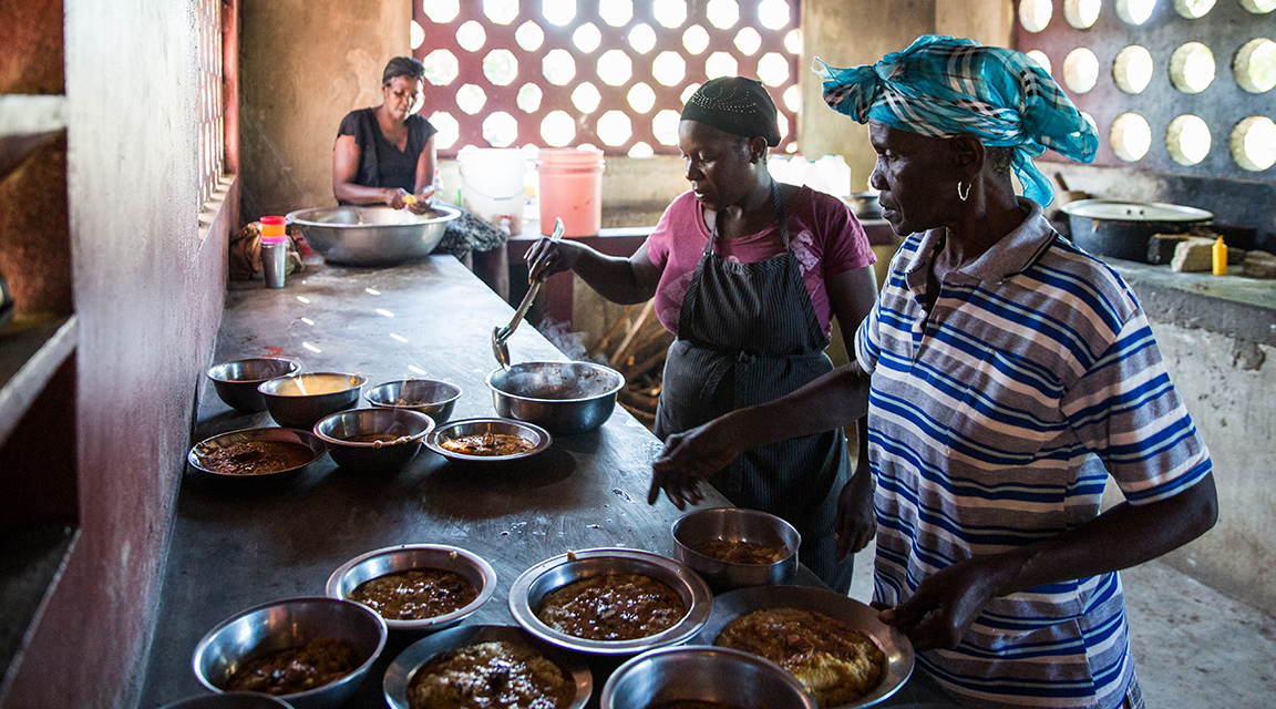 Women work in a kitchen to prepare school lunches