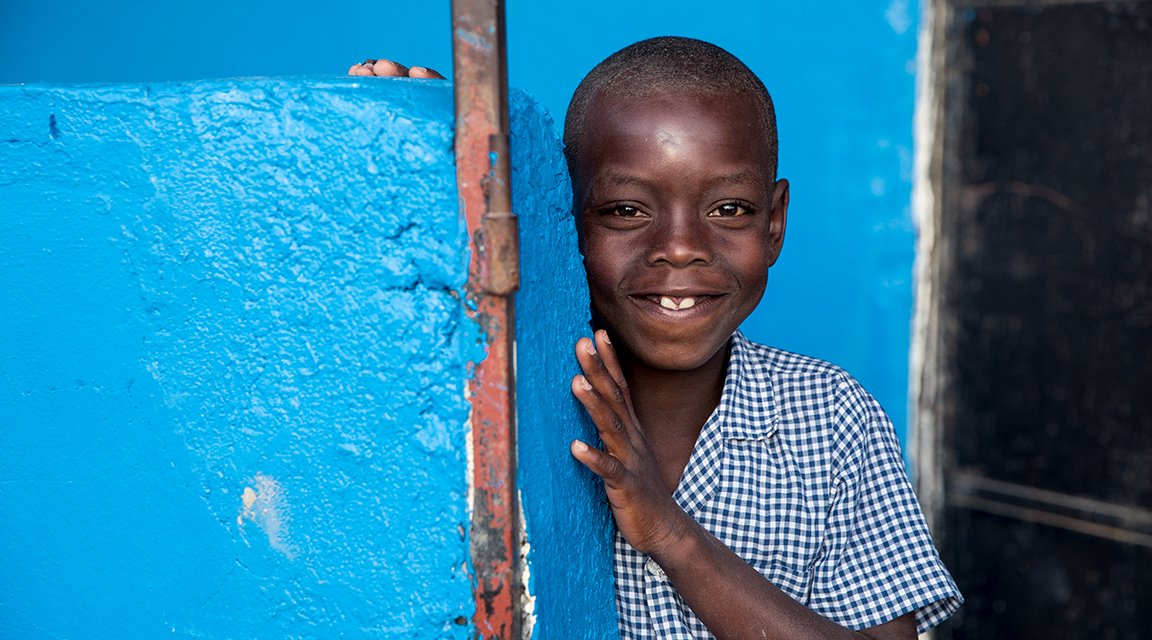 A student smiles outside a newly built school