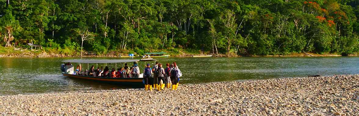 Travellers boarding a boat on a river in the rainforest