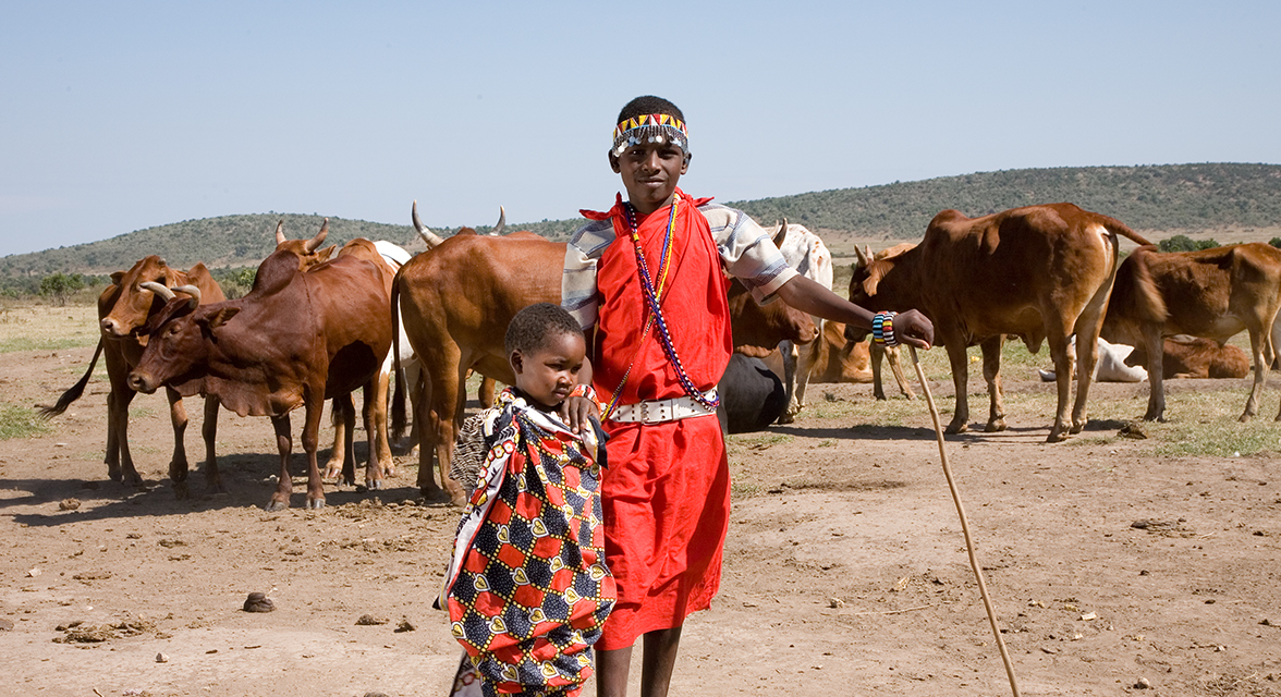 Young local boys in traditional clothing standing outside with cattle