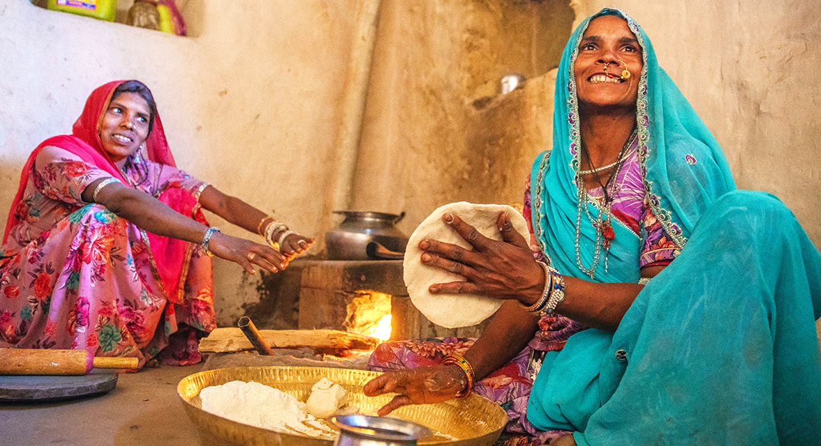 Local women cooking chapatti at home in India