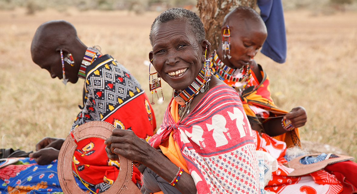 Local Kenyan women in traditional clothing beading in the grass