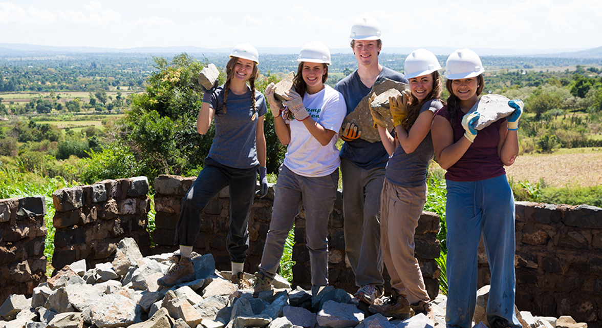 Young travellers posing for picture holding bricks against a wall they're building