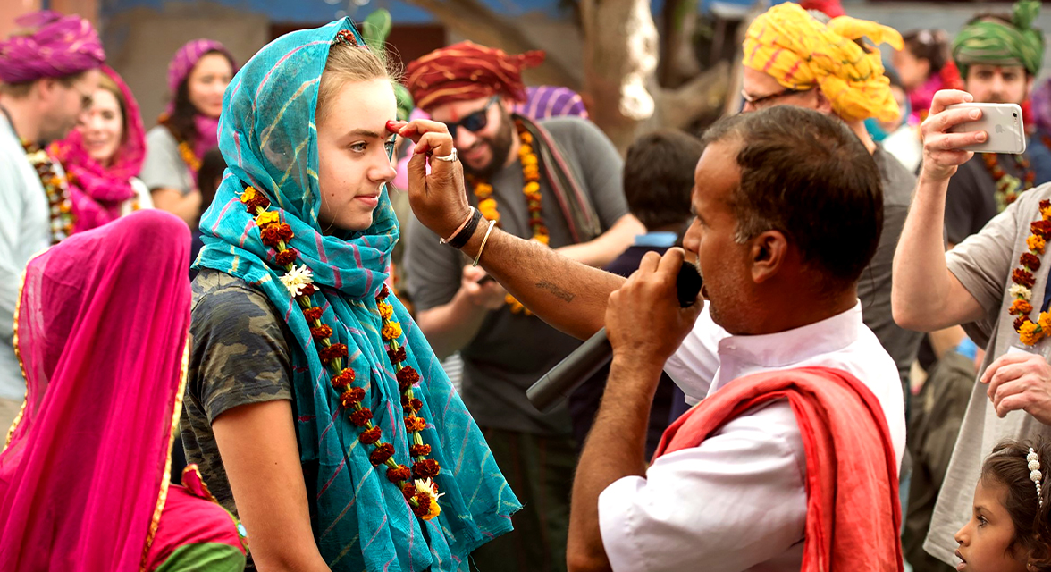 Young traveller taking part in a local tradition in India having her face painted on