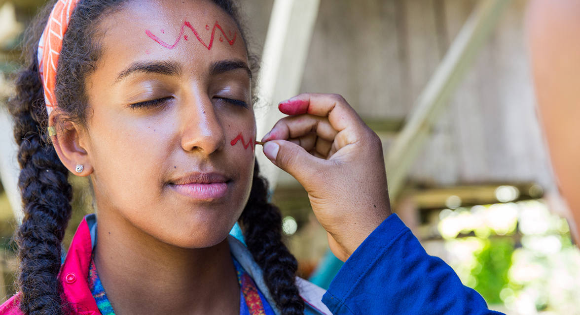 Young traveller taking part in an Ecuadorian tradition with her face being painted on