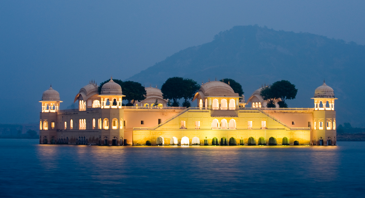 Exterior of luxurious accommodations in India lit at night against mountains