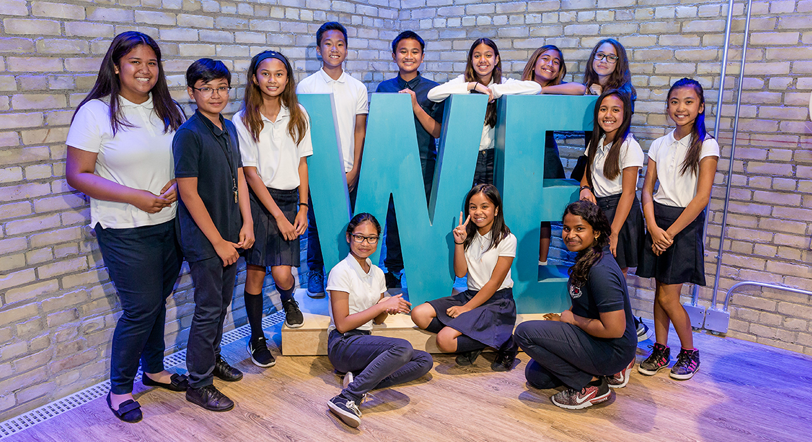 Students pose with the WE sign at the WE Global Learning Center