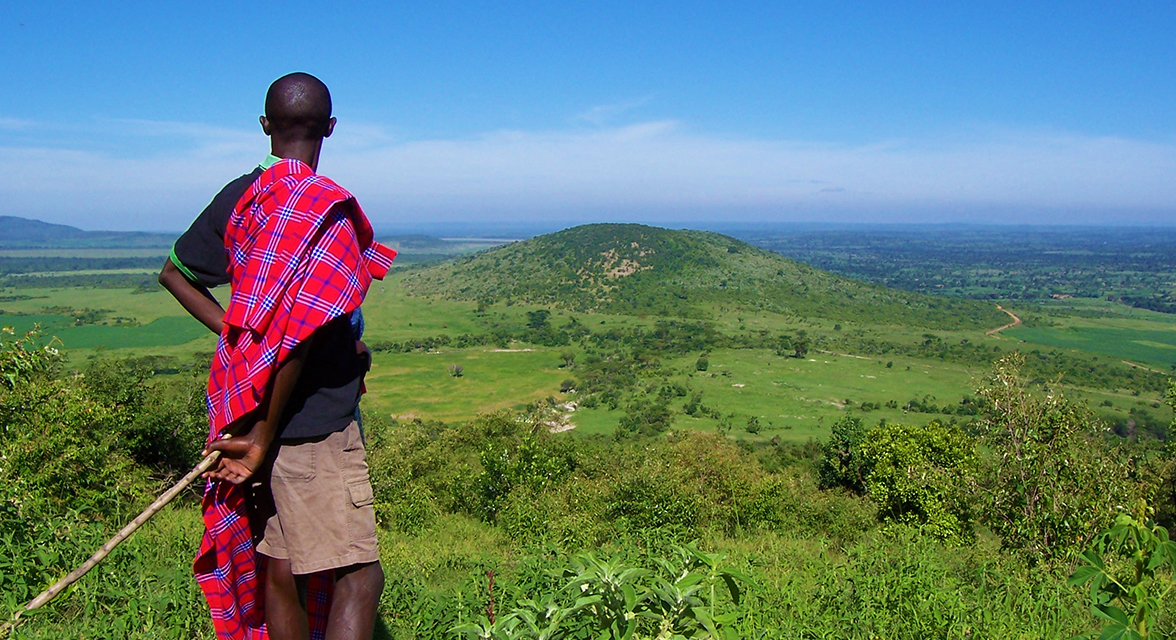 Young local man looking over hilly landscape in Kenya