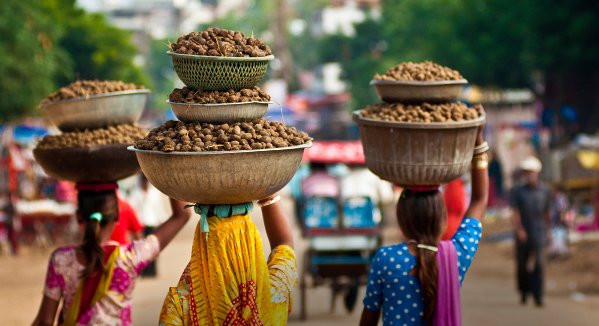 Local women balancing bowls of food on head, walking down street in India
