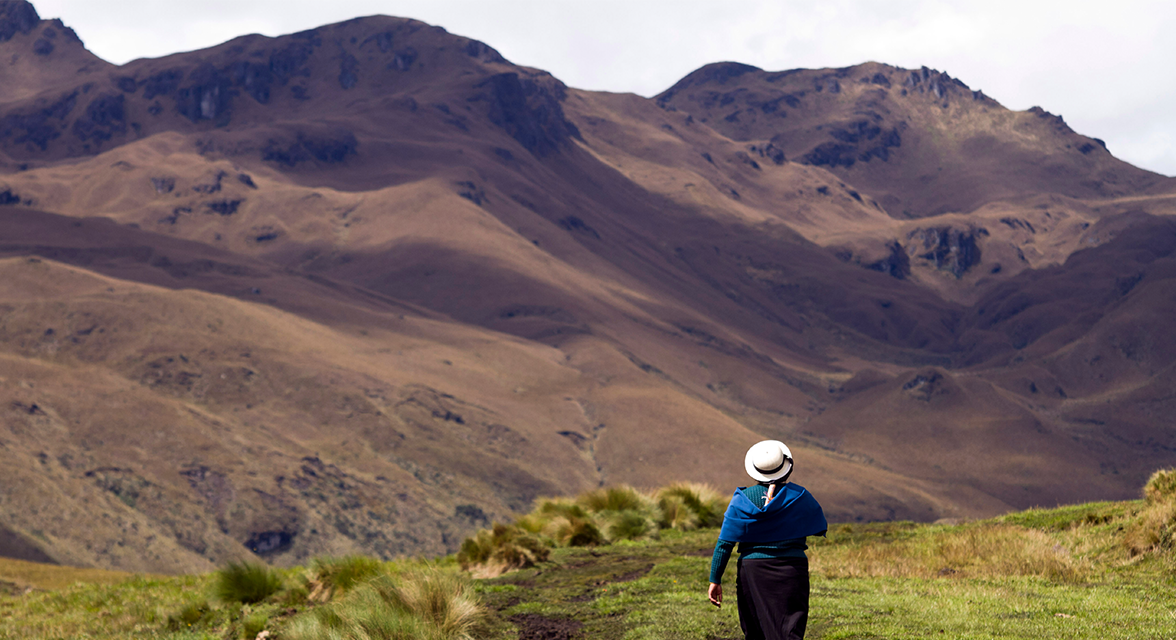Local woman walking across field against mountainous backdrop in Ecuador