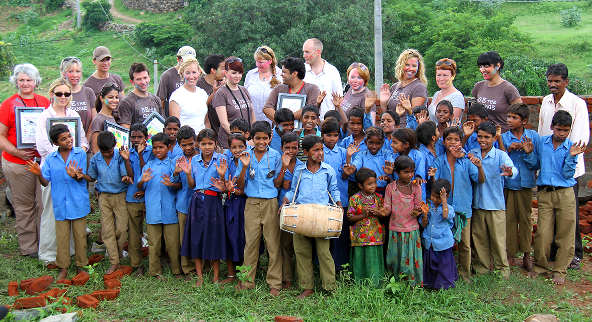 Group of travellers and local children in school uniforms posing for a picture in India outside in the grass