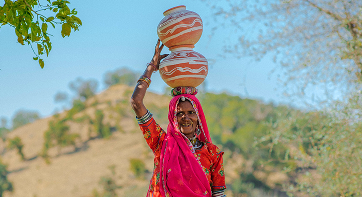 Local woman in traditional clothing balancing clay jugs on head in India