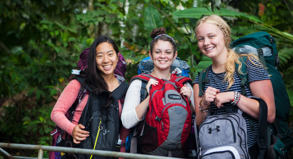 Young travellers posing for a picture in the rainforest with backpacks