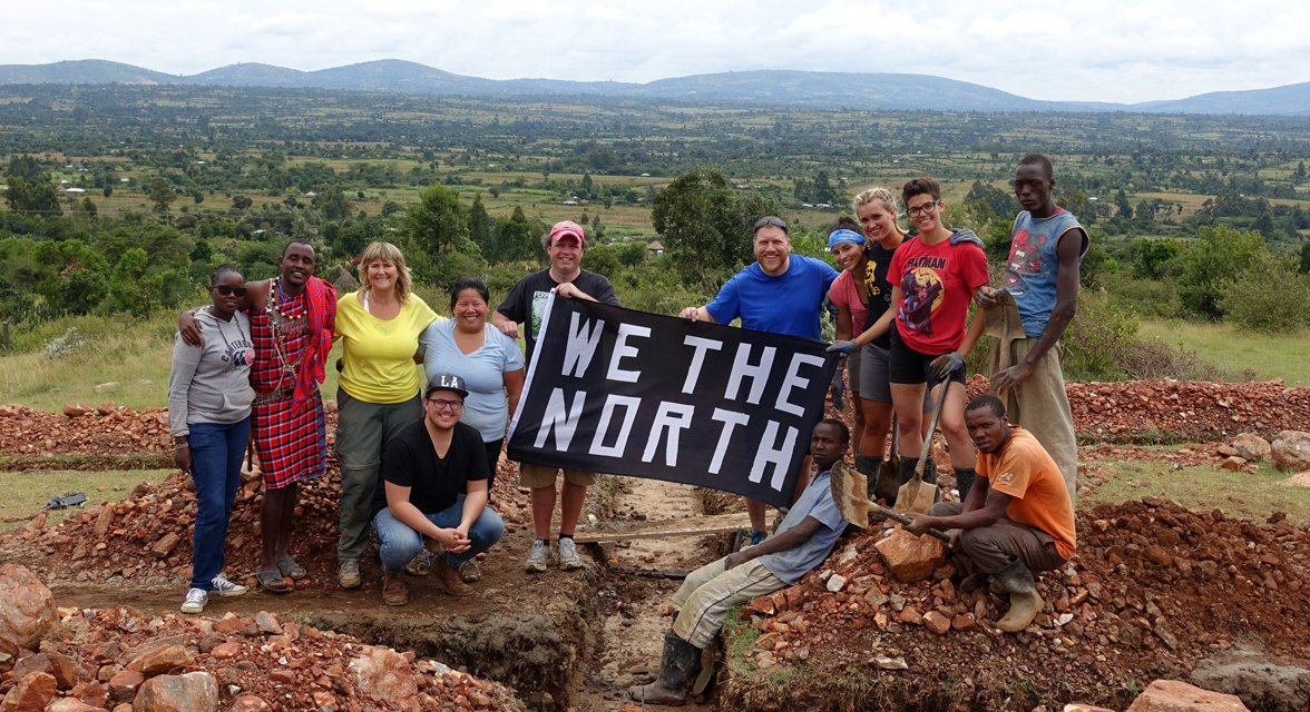 Locals with travellers holding up 'we the north' sign