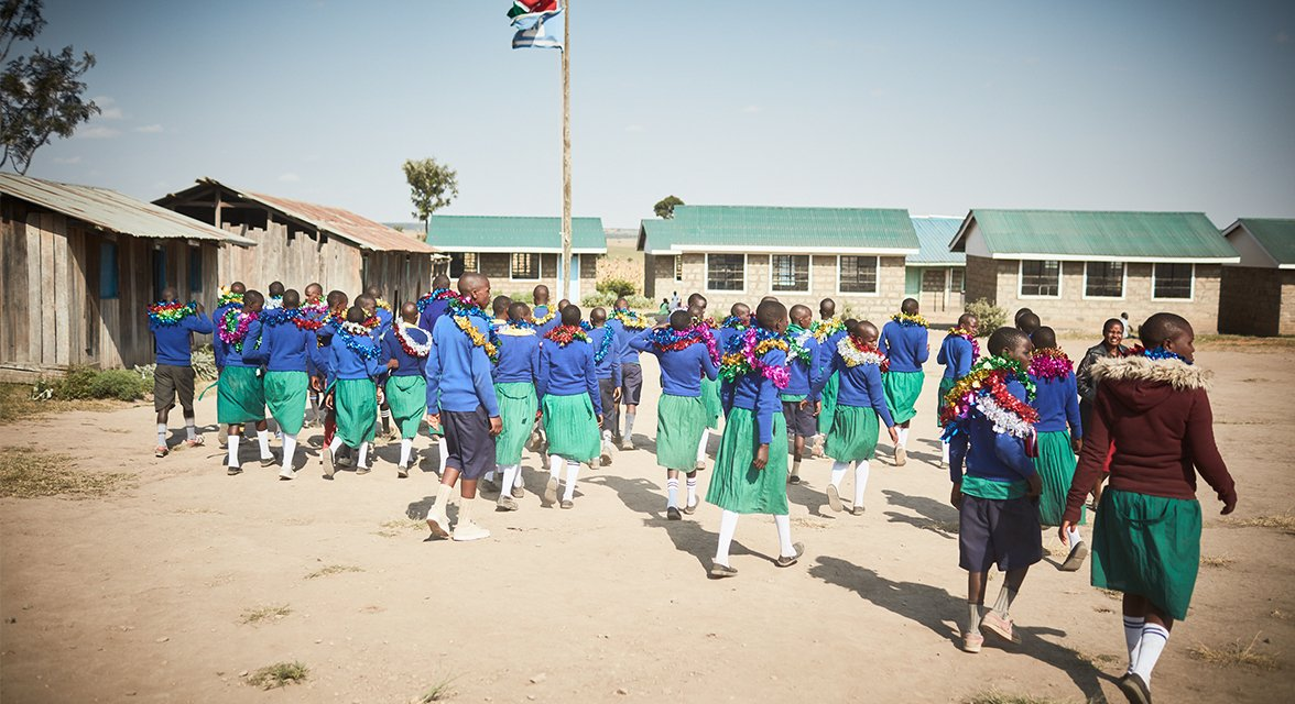 Local students celebrating in a WE Villages partner community school