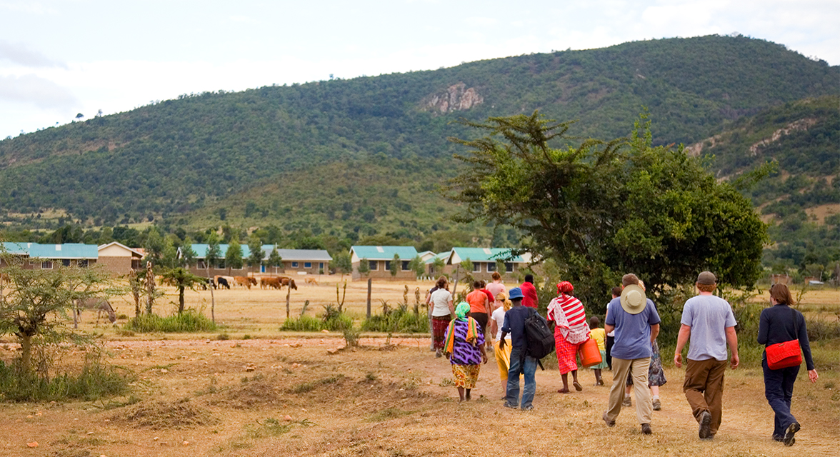 Group of travellers walking across the field in Tanzania