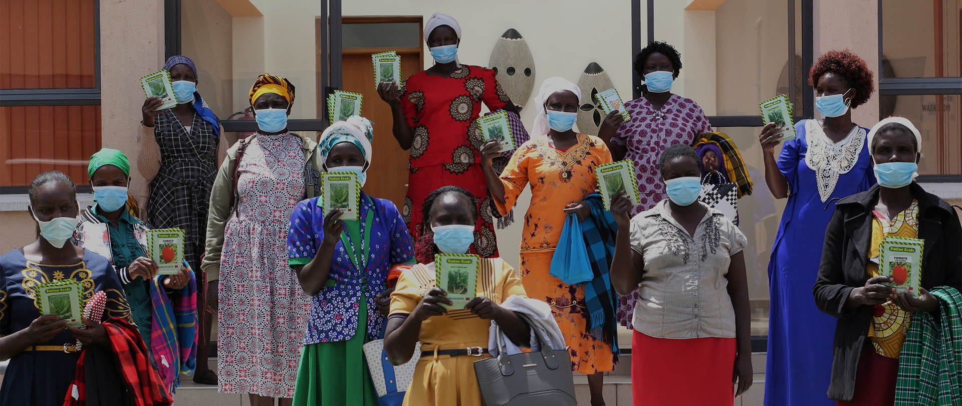 Kenyan mamas wearing face masks, holding up books.