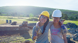Young travellers posing for a picture as they volunteer on a build site