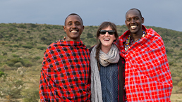 Local community members wearing shuka blanets and traveller posing for a picture in the savanna