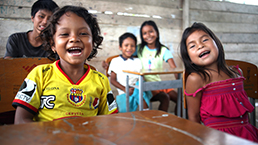 Young local students laughing and sitting inside a classroom in Ecuador