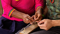 Local woman teaching traveller traditional beading using a small loom