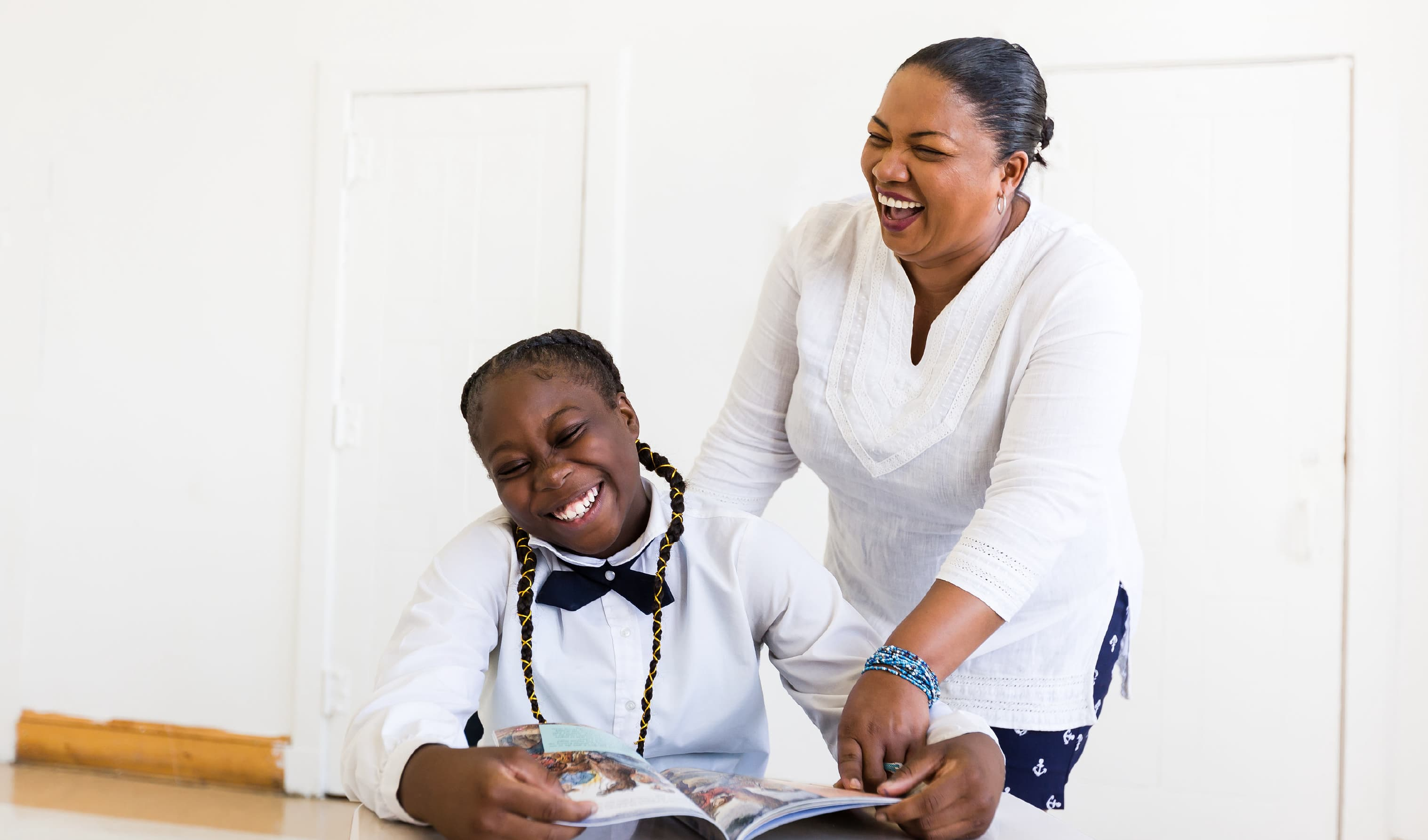 A student and teacher laughing together while reading a book