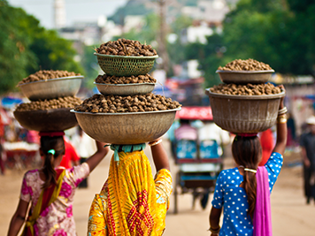 Local women walking and balancing bowls filled with food on their heads in India