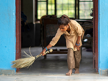 A young girl sweeping the floor