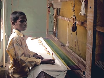 A young boy working in textile production