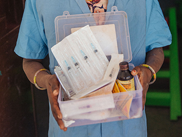 A nurse holding a container of medicine
