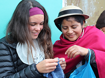 Local woman in traditional clothing teaching young traveller how to knit in Ecuador