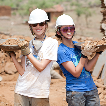 Smiling travellers carrying rocks at a building site