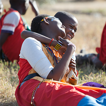 Local Kenyan women in traditional clothing hugging in the grassy field