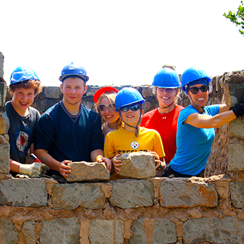 Travellers building a wall on a development project