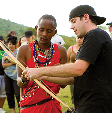 Maasai Warrior teaching travellers about traditional Maasai bow and arrow weapon