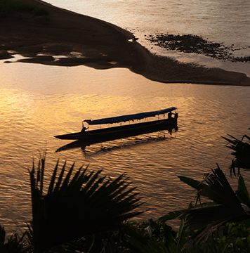 Scenic view of boat in Napo River at sunset