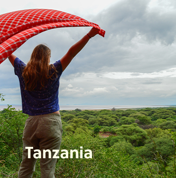 Traveller looking over the grassy plains of Tanzania holding a shuka blanket