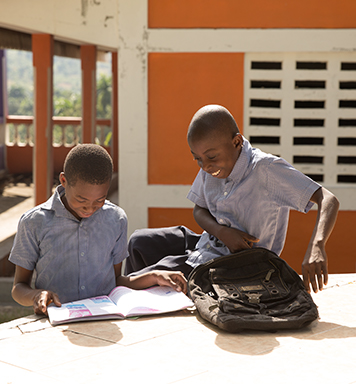 Haitian students study outside a school built by WE.