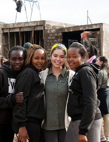 Auli'i smiles with three students in Kenya.