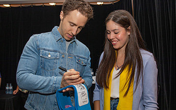 Craig Kielburger signs one of Maddison's scarves.