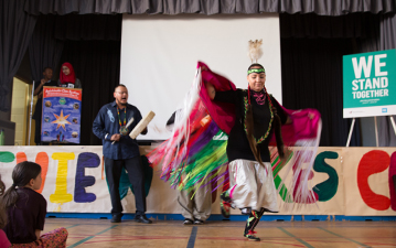 Indigenous student performing an Indigenous dance at school for WE Stand Together campaign
