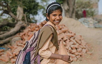 A girl going to school, wearing a backpack, smiling at the camera