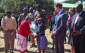 The First Lady of Kenya shakes hands with a student.