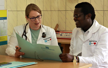 Medical staff consult with one another sitting at desk at Baraka Hospital in Kenya